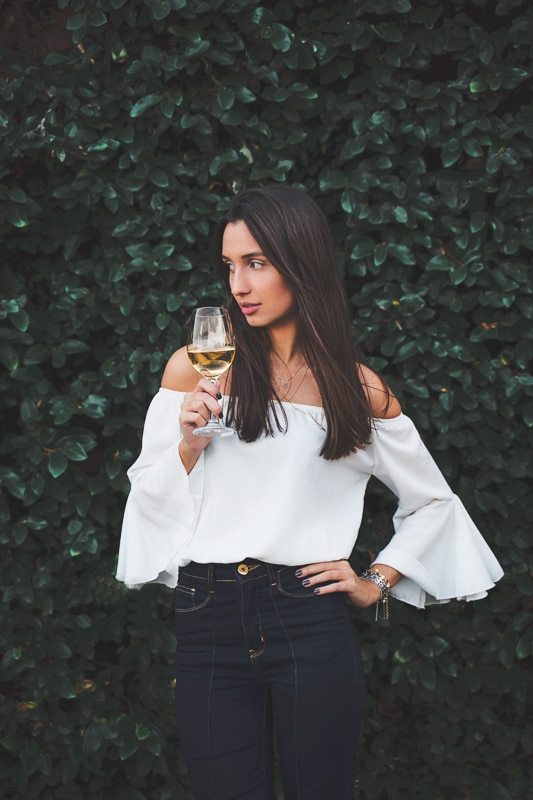 woman in off the shoulder top holding a glass of white wine