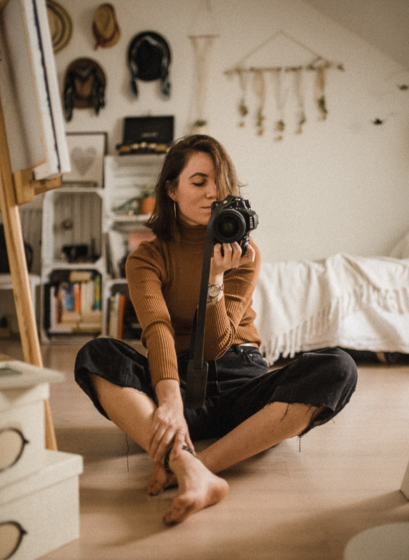 woman sitting on carpet playing with a camera
