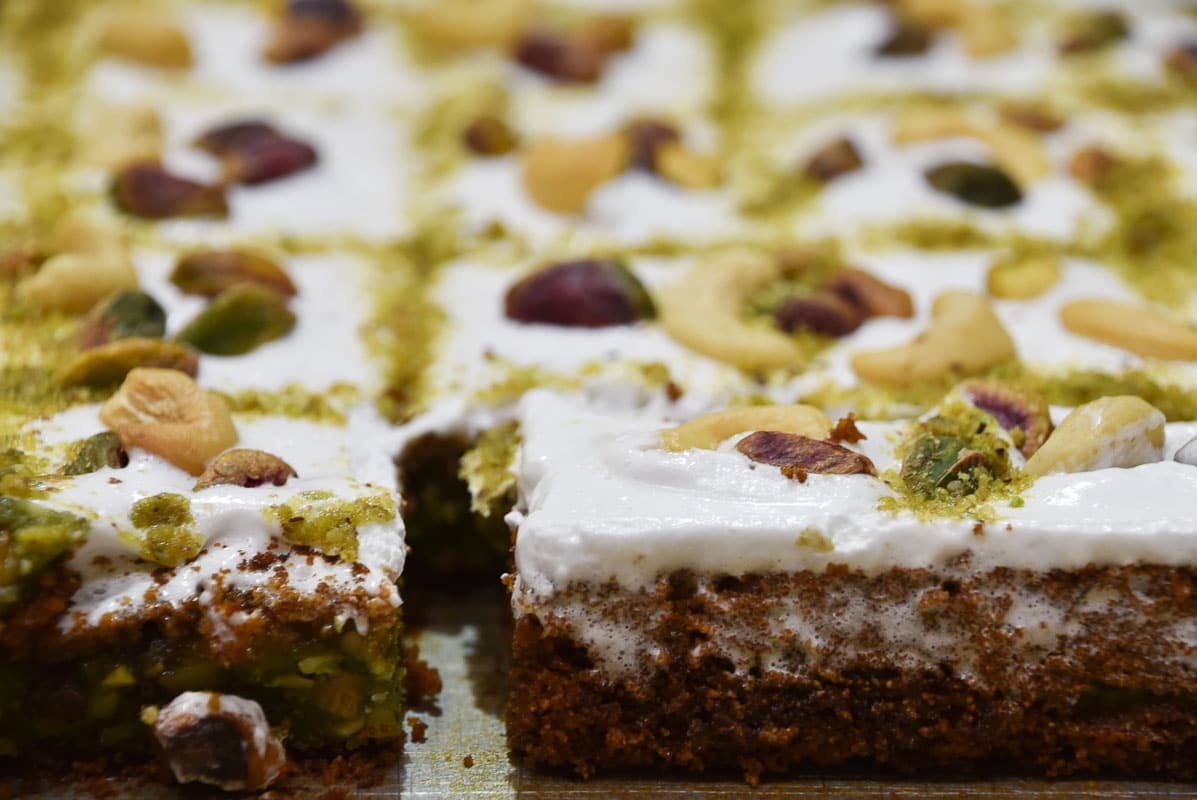 arabian sweet cake with white icing and pistachio up close