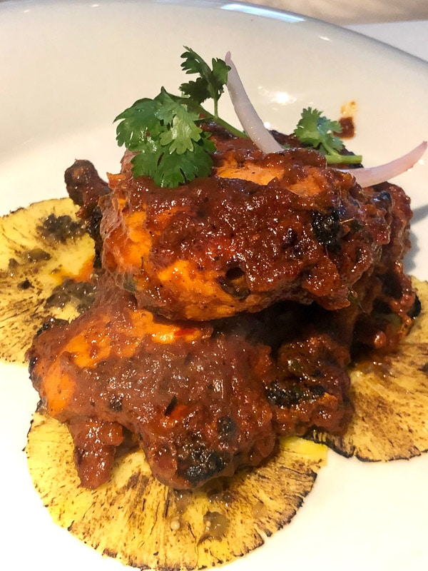 chicken in mango sauce with pineapples on white plate