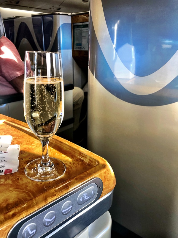 glass of champagne on seat side rest emirates business class