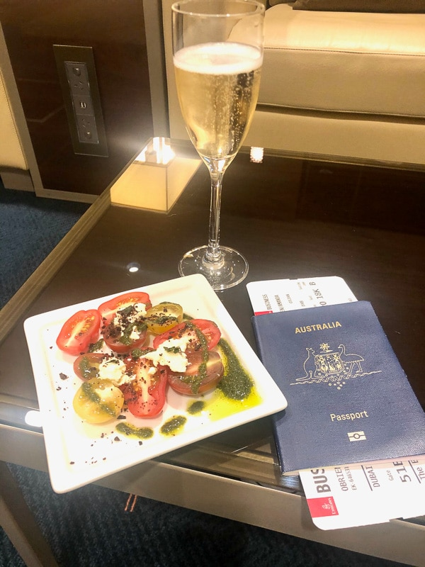 glass of champagne, plate with tomatoes and australian passport
