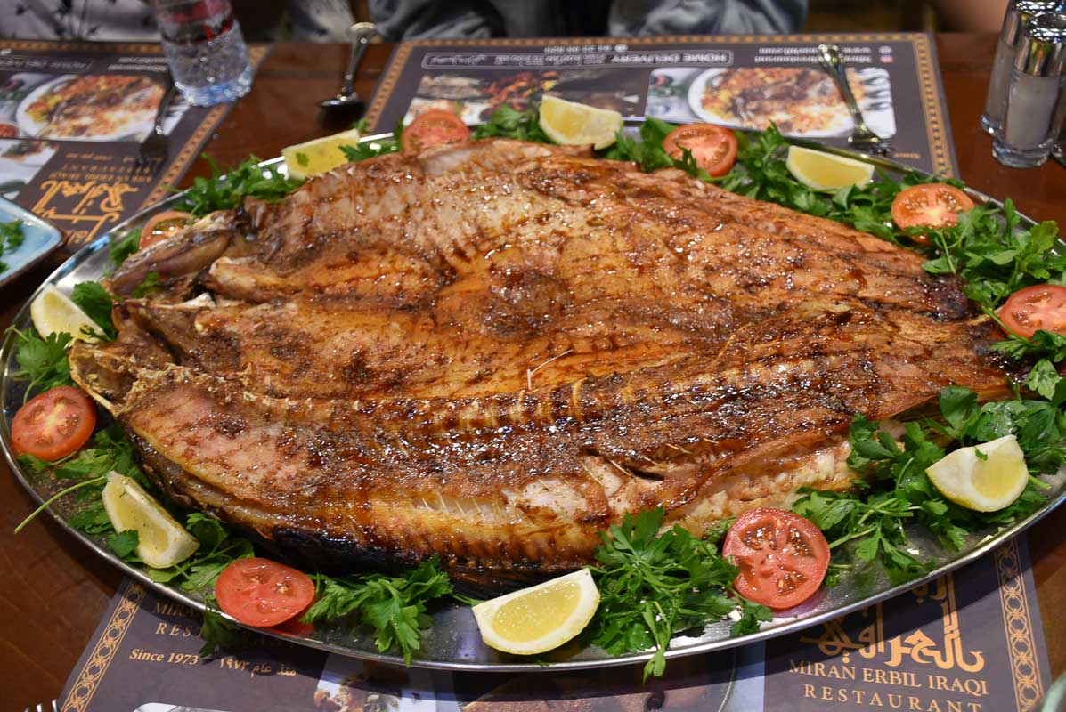 large grilled fish presented on a steel plate