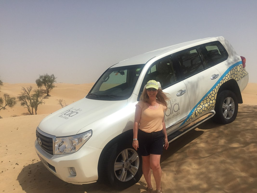 woman in front of 4 wd in desert
