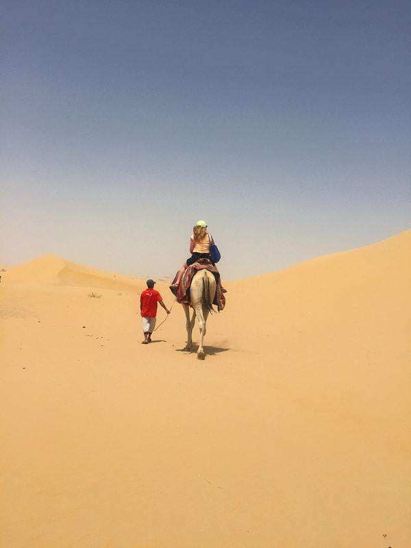 woman on camel being led by man from behind in the distance