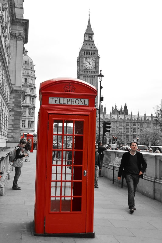 Red phone booth against london landmark big ben in black and white