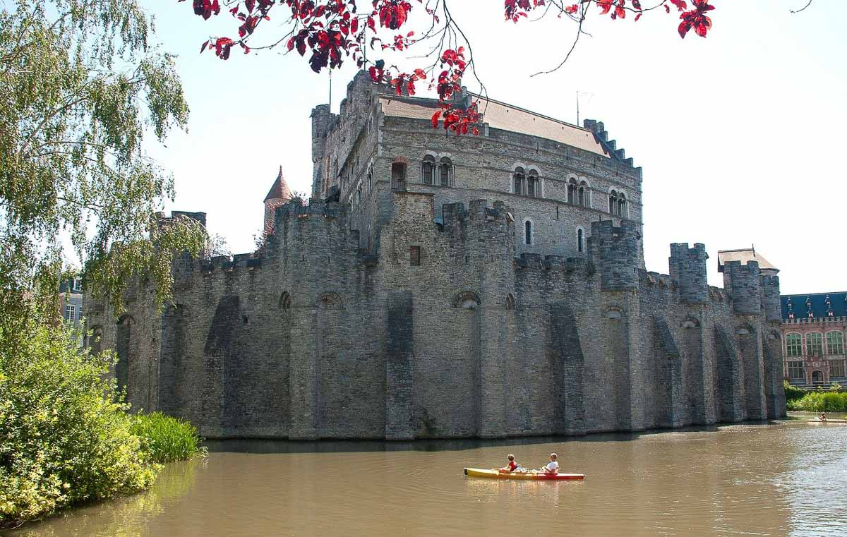 Castle of Gravensteen with moat and people in canoe