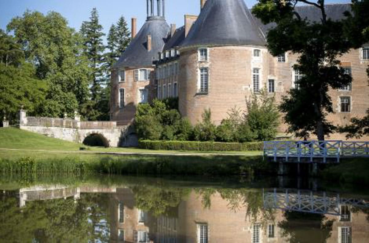 chateau de saint fargeau with partial reflection in moat france
