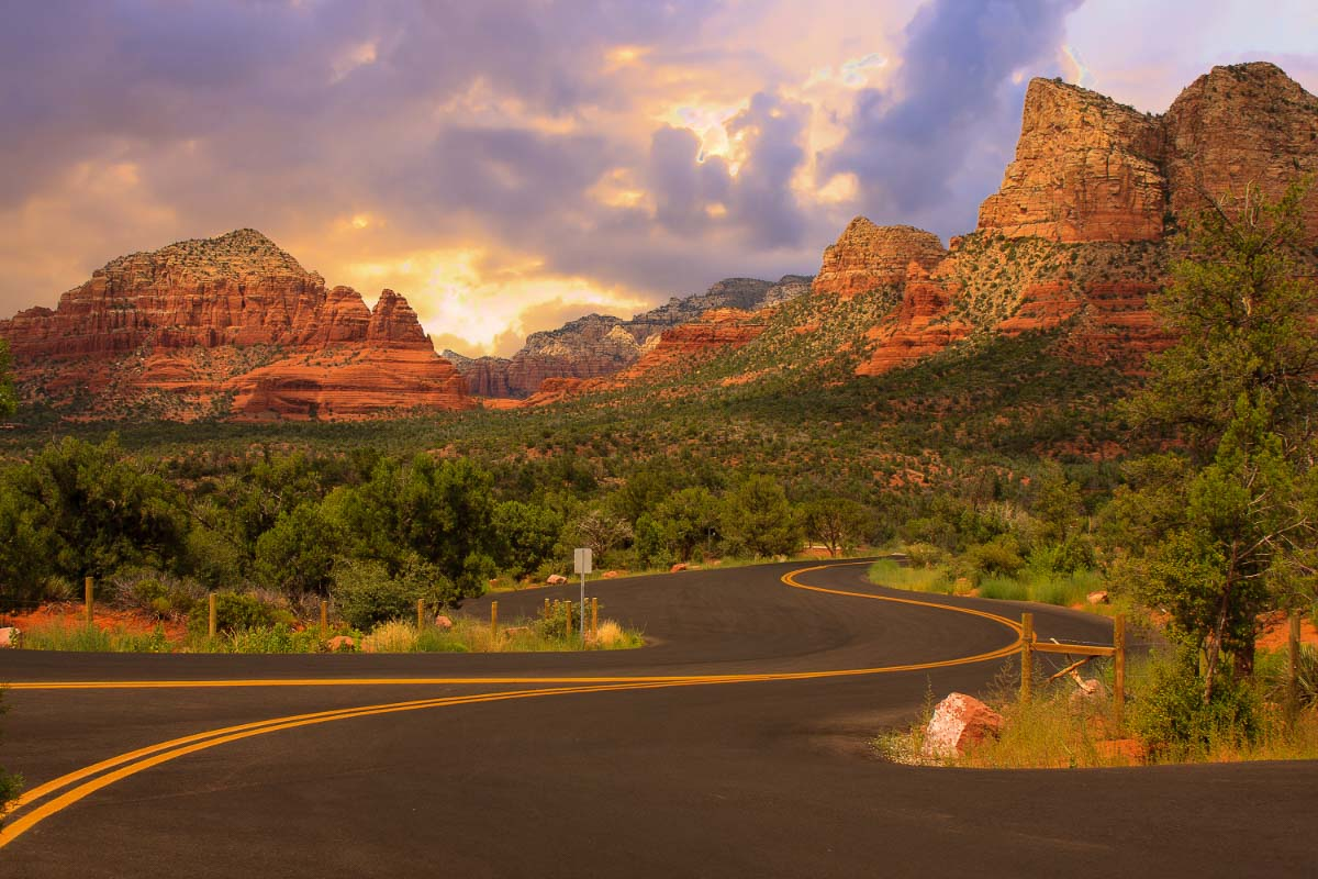 road with rocks of sedona behind at sunset