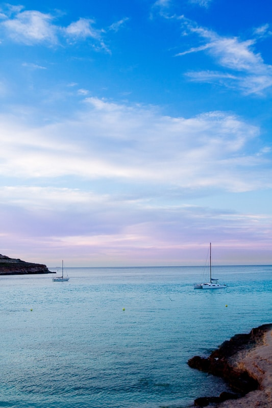 cala conta beach ibiza with sailboat