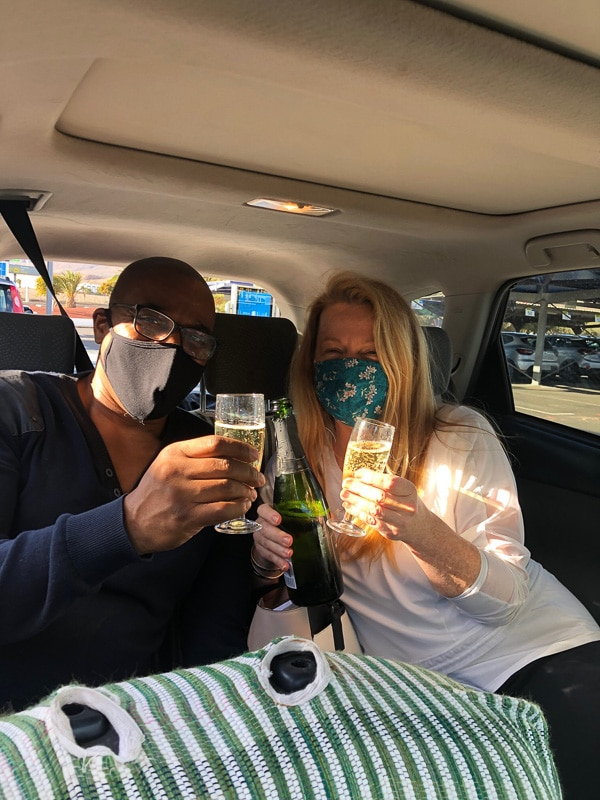 couple in back of car with glasses of cava wearing masks