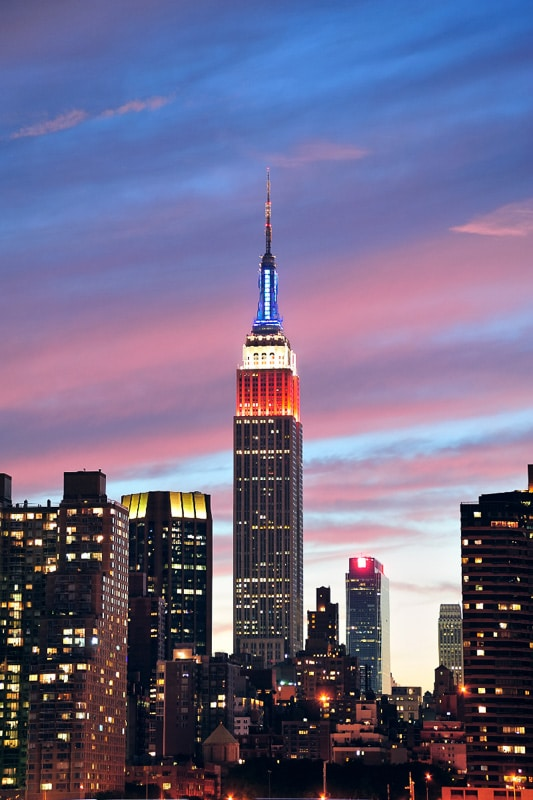 empire state building lit up against twilight sky