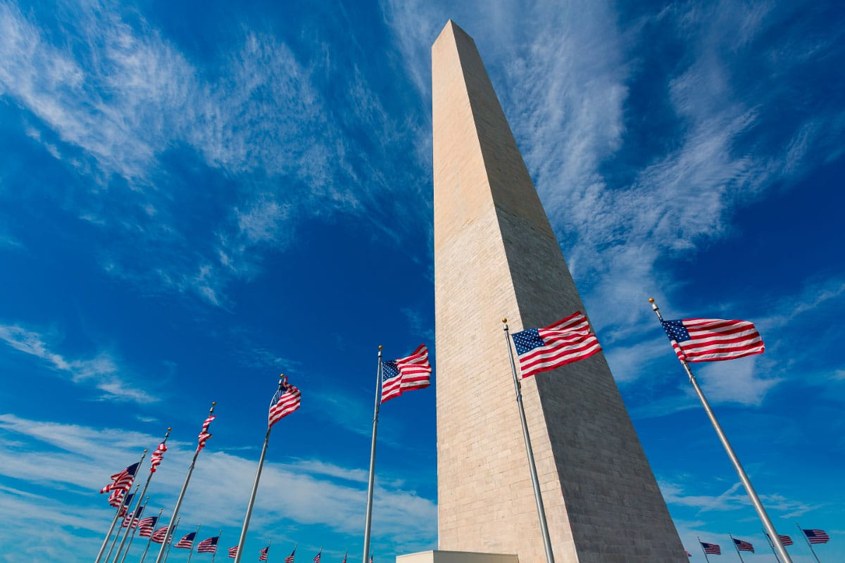 washington monument against blue sky with american flags