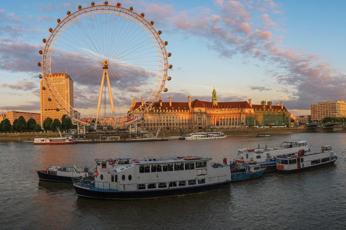 boats on the thames and the eye sunset in london